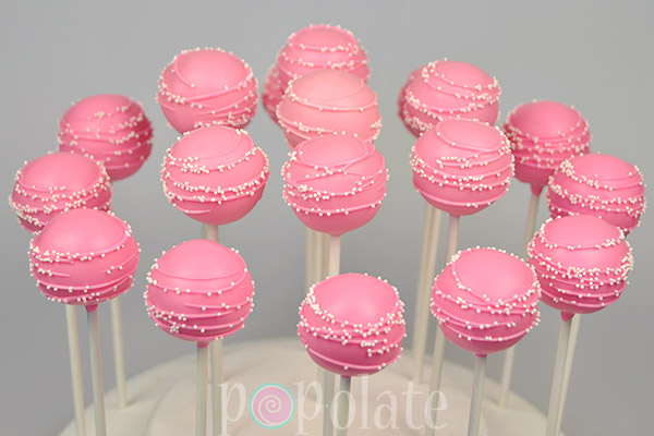 Pink drizzle with mini sprinkles non-pareil cake pops